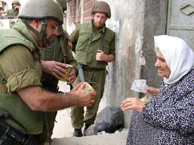 An Israeli soldier giving food to a Palestinian woman